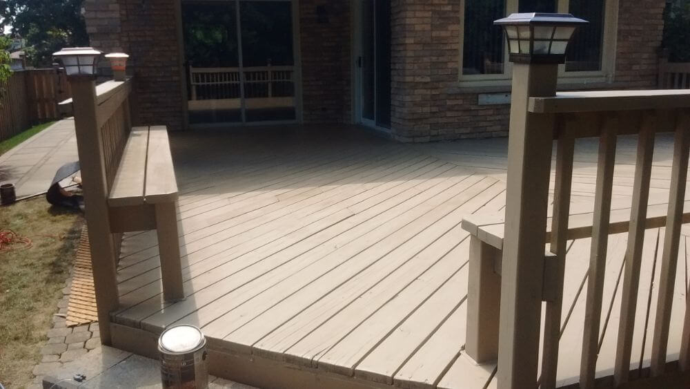 wooden deck with integrated benches and lanterns on posts