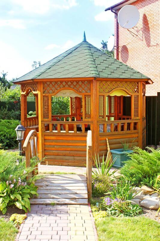 wooden gazebo with green shingles